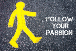 39852431 - yellow pedestrian figure on the road walking towards follow your passion. conceptual image with text message over asphalt background.